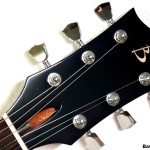 Ebony headstock veneer close up with Maple headstock logo inlay