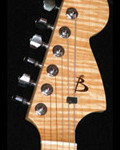 Lefty strat shaped handcrafted guitar, flamed Maple headstock close up with Rosewood logo inlay.